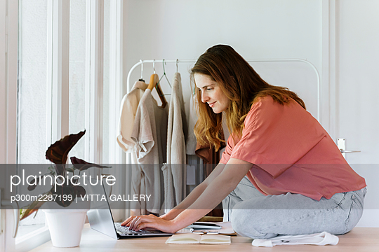 Female professional using laptop while sitting on table at home - p300m2287199 by VITTA GALLERY