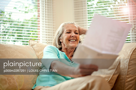 Happy senior woman reading letter while sitting on sofa in living room - p300m2287251 by LOUIS CHRISTIAN