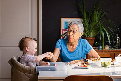 Senior asian woman feeding toddler grandaughter at table at home - p1166m2285624 by Cavan Images