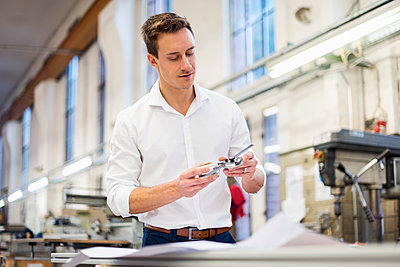Young businessman in factory holding component - p300m1563280 by Daniel Ingold