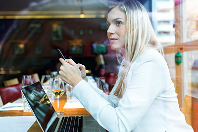 Businesswoman using laptop and cell phone in a restaurant - p300m2140673 by Josep Suria