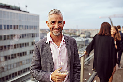 Portrait of smiling businessman holding wineglass with coworkers in background on terrace - p426m2146273 by Maskot