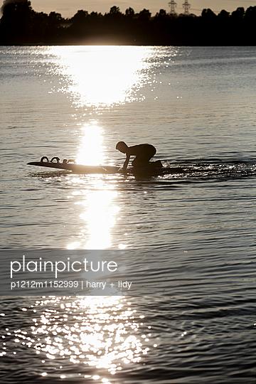 Junge paddelt mit dem Surfbrett - p1212m1152999 von harry + lidy