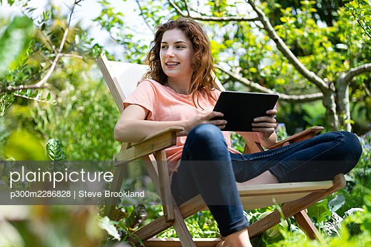 Young woman sitting in garden chair in beautiful organic garden and holding a tablet in Portugal - p300m2286828 von Steve Brookland