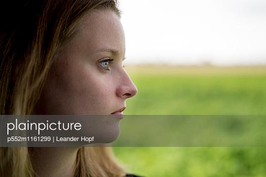Junge Frau blickt aus dem Fenster - p552m1161299 von Leander Hopf