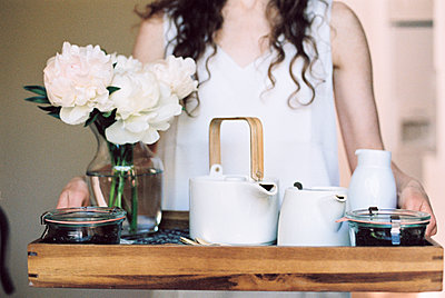 Woman carrying a tray with a teapot and a vase of white roses. - p1100m1080253 by Mint Images