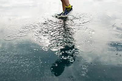 Low section of boy jumping in puddle - p1166m1186133 by Cavan Images