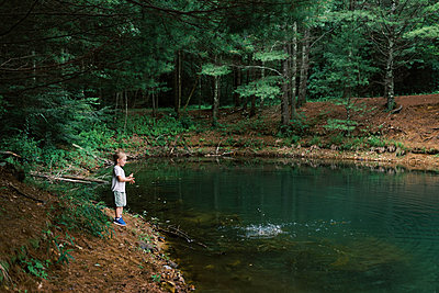 Little boy throwing sticks and rocks into a pond. - p1166m2151846 by Cavan Images