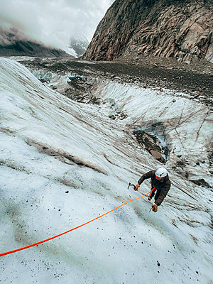 High angle shot of man climbing a steep ice face with ice axes - p1166m2212338 by Cavan Images