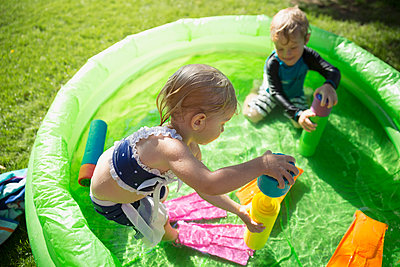Brother and sister playing with squirt guns in sunny wading pool - p1192m1184004 by Hero Images