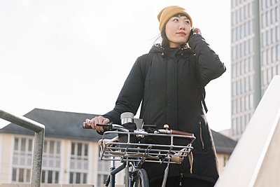 Woman with bicycle on the phone in the city, Frankfurt, Germany - p300m2179996 by Hernandez and Sorokina