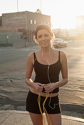 Smiling woman holding jump rope standing on sidewalk in city at sunset - p300m2240008 by LOUIS CHRISTIAN