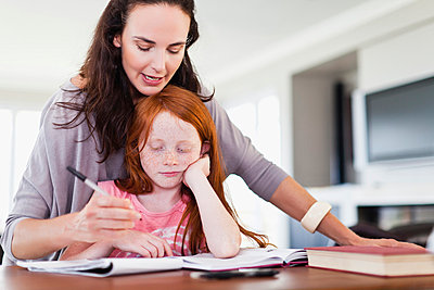 Mother helping daughter with homework - p429m800881f by Hybrid Images