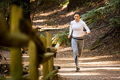Woman running on forest path - p555m1303595 by Adam Hester
