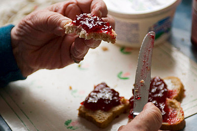 Hands of a senior woman with slice of bread and jam - p8960593 by Theo van Pelt