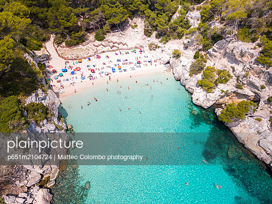 Aerial view of Cala Macarelleta beach crowded in summer, Menorca, Balearic Islands, Spain - p651m2104724 by Matteo Colombo photography