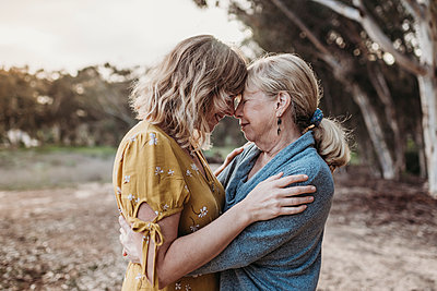 Lifestyle portrait of adult mother and senior mother embracing - p1166m2205645 by Cavan Images
