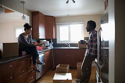 Young couple moving into new house, taking coffee break and unpacking cardboard boxes in kitchen - p1192m1559967 by Hero Images