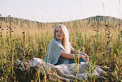 Beautiful blond woman sits in a field - p1363m1491694 by Valery Skurydin