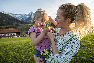 Austria, Tyrol, Walchsee, mother carrying daughter with flowers on an alpine meadow - p300m2029385 von Johanna Lohr