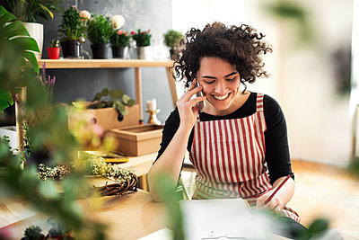 Happy young woman on the phone in a small shop with plants - p300m2143811 von HalfPoint