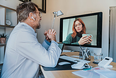 Male doctor talking over computer with patient through video call at clinic - p300m2267712 by Mareen Fischinger