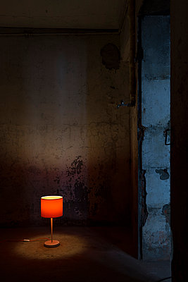 Table lamp in deserted building - p335m1041630 by Andreas Körner