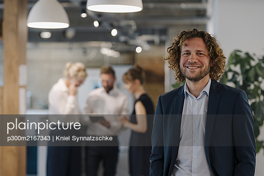 Portrait of confident businessman in office with colleagues in background - p300m2167343 by Kniel Synnatzschke
