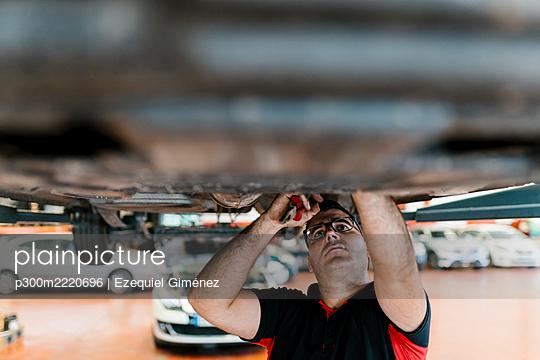 Mid adult man examining car in auto repair shop - p300m2220696 by Ezequiel Giménez
