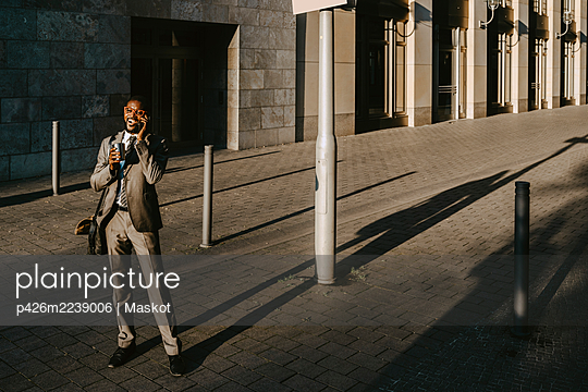 Male entrepreneur talking on smart phone while standing on footpath during sunny day - p426m2239006 by Maskot