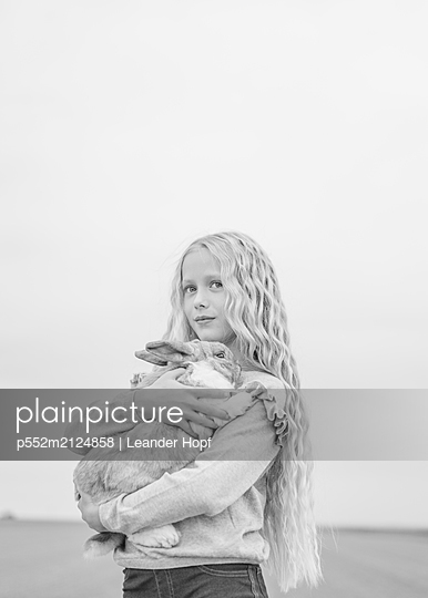 Blonde girl holding rabbit in arms - p552m2124858 by Leander Hopf