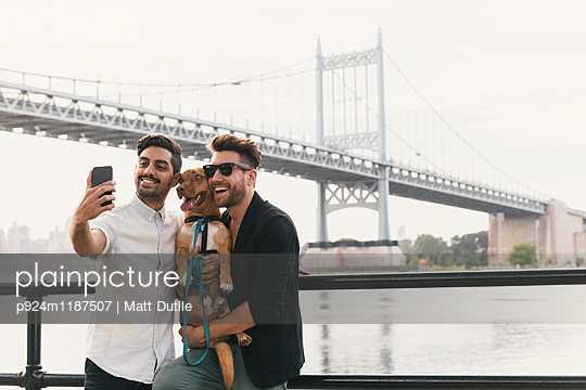 Young male couple on riverside taking smartphone selfie with dog, Astoria, New York, USA