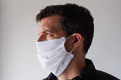 Man wearing homemade cloth face mask during Covid 19 pandemic. - p1166m2174102 by Cavan Images