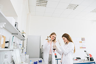 Scientists in white coats doing experiment in lab - p300m2250195 by Hernandez and Sorokina