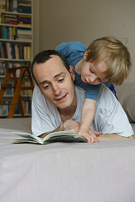Father and son reading book while lying on bed at home - p301m1148402 by Halfdark