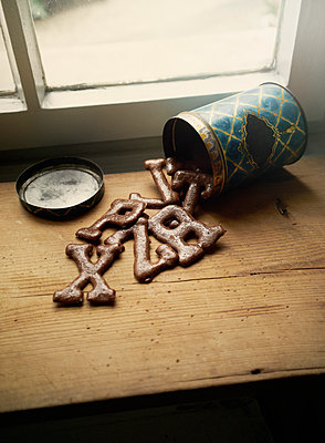 High angle view of alphabet cookies spilling from can on table by window - p301m1482555 by Benne Ochs