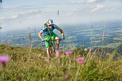 Mountain biker riding on Alpine trail - p1026m786142f by Robert Niedring