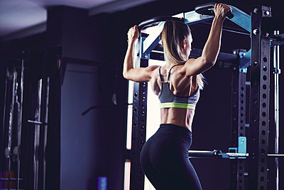 Rear profile of young woman doing chin ups at fitness centre - p1166m2095471 by Cavan Images