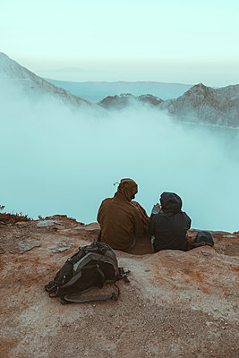 Two hikers sitting and looking at Ijen lake - p1166m2137437 by Cavan Images