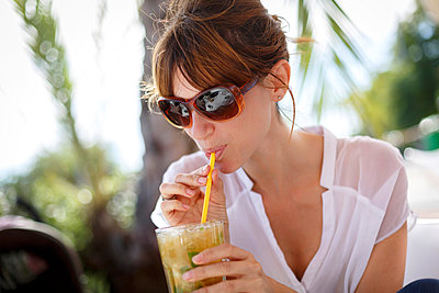 Mid adult woman drinking orange juice at pavement cafe, Castelldefels, Catalonia, Spain - p429m1013739f by Quim Roser