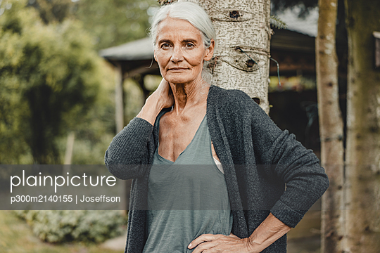 Senior woman standing in nature, portrait - p300m2140155 by Joseffson