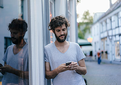 Man looking at cell phone in the city - p300m1535893 by Kniel Synnatzschke