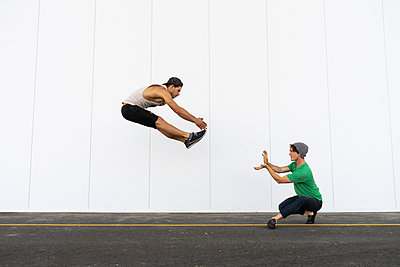 Two acrobats doing tricks together, jumping mid-air - p300m2012361 von VITTA GALLERY