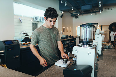 Barista preparing coffee in a coffee bar - p300m2012916 von Oriol Castelló Arroyo