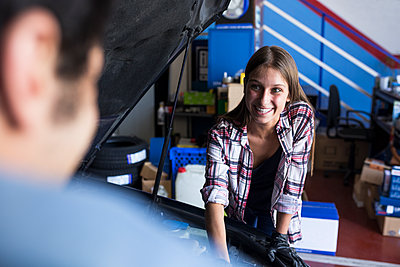 Cheerful young woman working in service station and looking at anonymous man while fixing car engine - p300m2155102 by Andrés Benitez