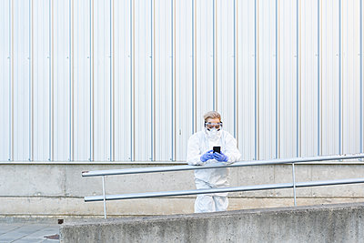 Female scientist wearing protective suit and mask and using smartphone - p300m2170950 by Eloisa Ramos