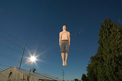 Young man jumping in mid-air, low angle view - p4341686 by Alin Dragulin