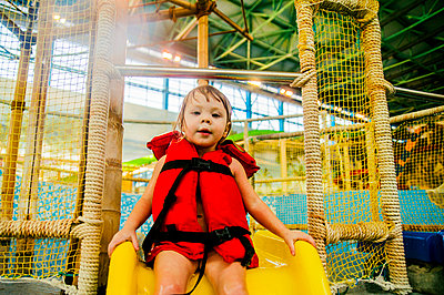 Caucasian girl riding slide at water park - p555m1306022 by Aleksander Rubtsov