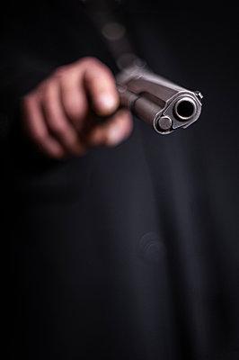 Man aiming with pistol - p971m2142776 by Reilika Landen