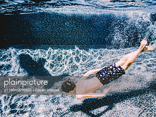 8 years old boy swimming with the shadow of a dolphin in a pool - p1166m2292651 by Cavan Images